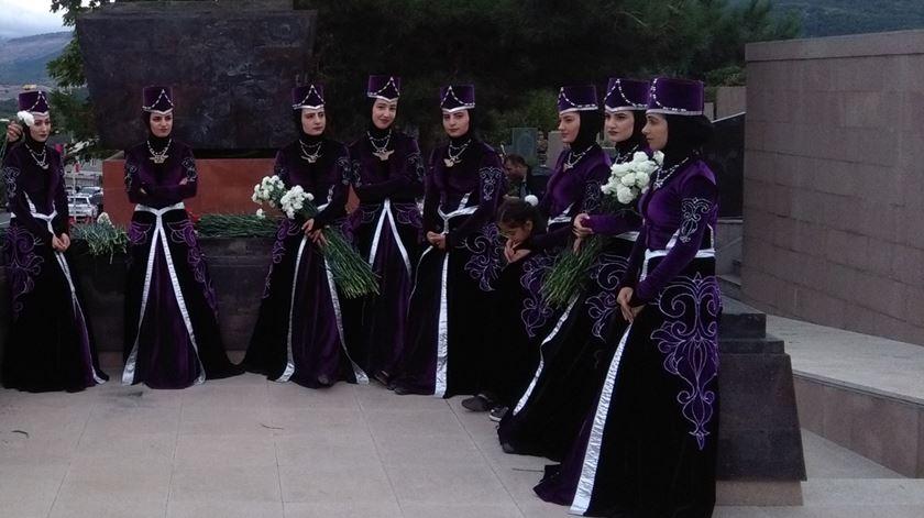Mulheres de Nagorno Karabakh, com traje típico, prestam homenagem a mortos na guerra. Foto: Filipe Avillez/RR